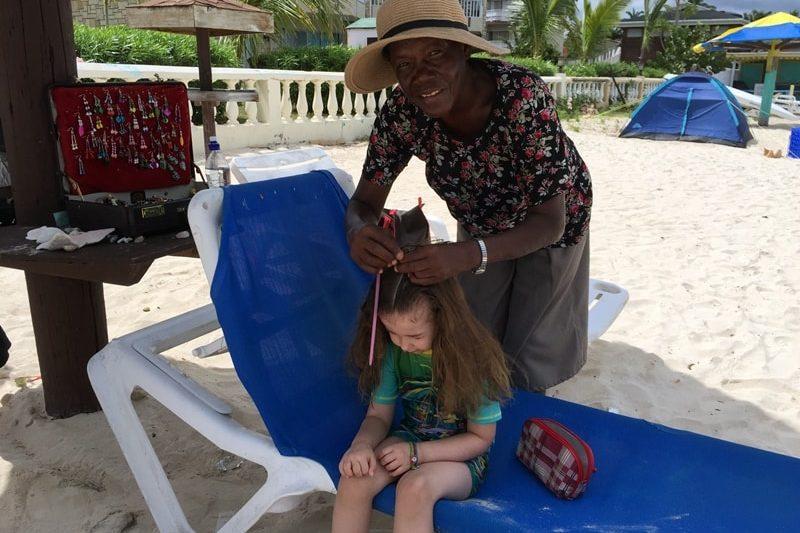 Mädchen dem am Strand Rastazöpfe geflochten werden
