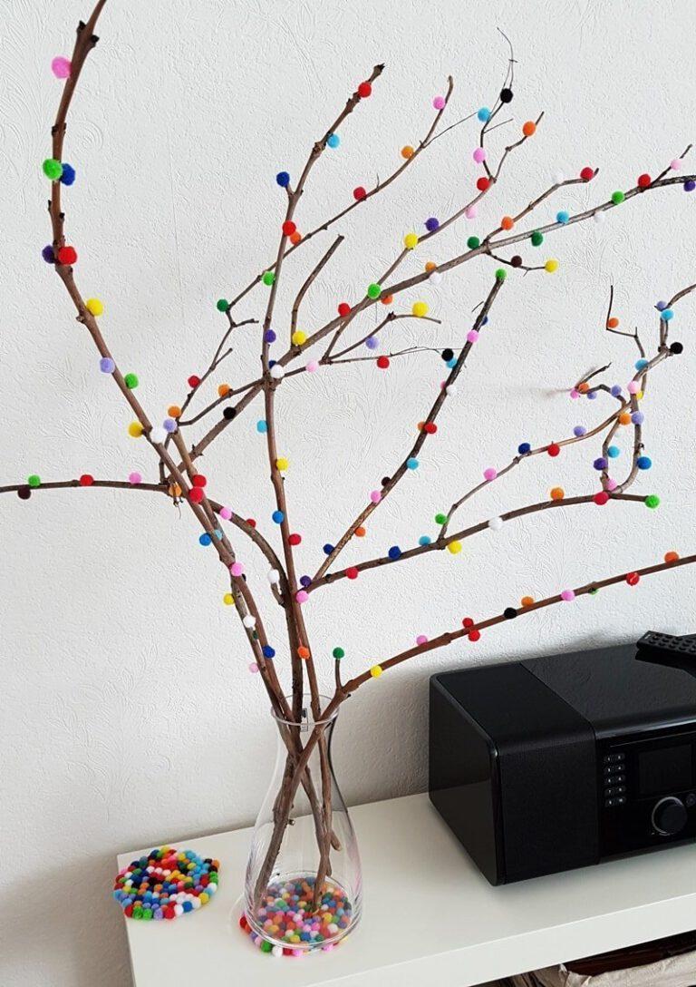 Dekorativer Zweig beklebt mit Pompons