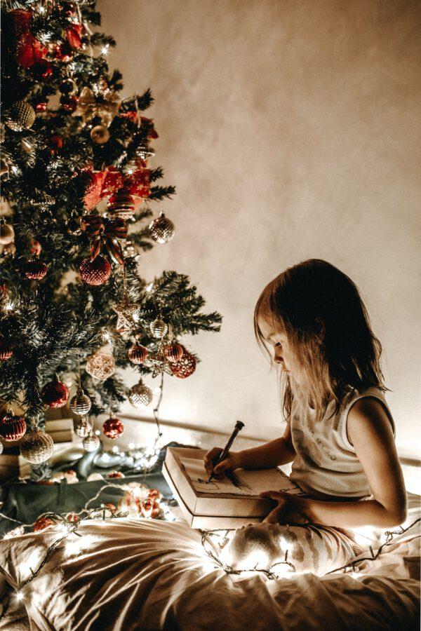 Kind sitzt vor Weihnachtsbaum